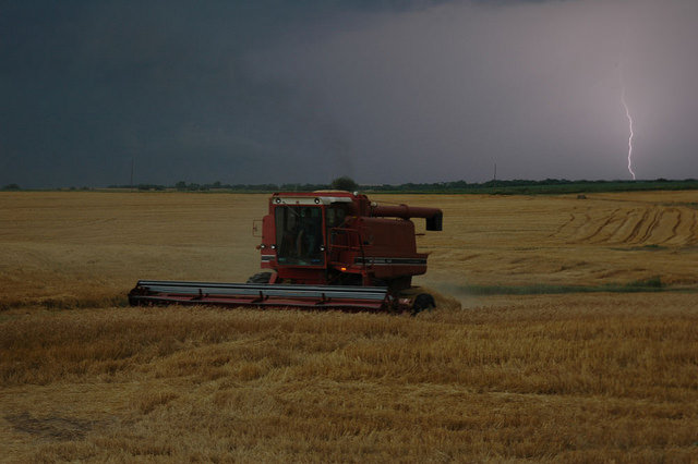 A lightning bolt strikes behind a combine trying to finish wheat harvest